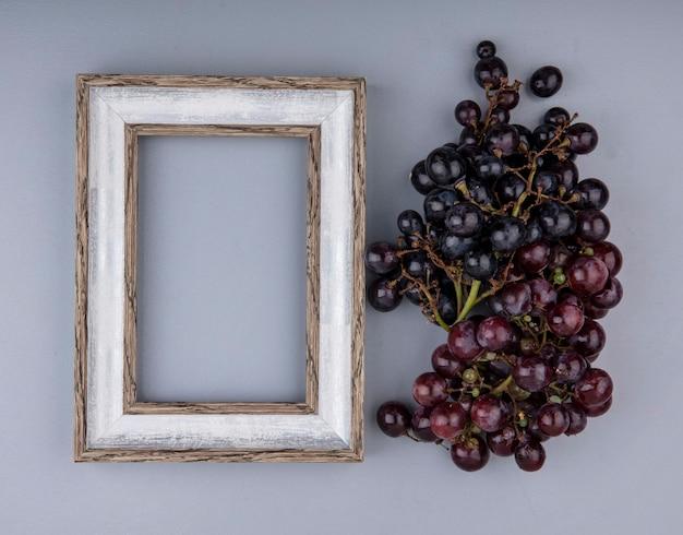 Bovenaanzicht van bos van zwarte druiven en frame op grijze achtergrond met kopie ruimte