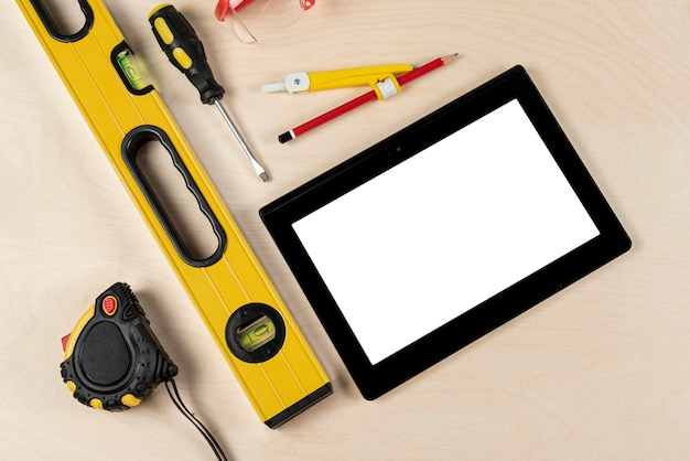 Bovenaanzicht van bouwer bureau met tablet mock-up