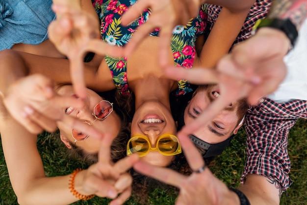 Bovenaanzicht van bovenaf op kleurrijke stijlvolle gelukkig jong gezelschap van vrienden liggend op gras in park, man en vrouw samen plezier