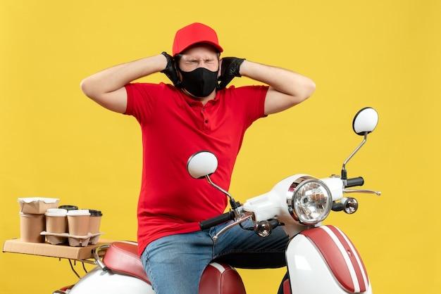 Bovenaanzicht van boze jonge volwassene dragen rode blouse en hoed handschoenen in medisch masker leveren bestelling zittend op scooter zijn oren sluiten op gele achtergrond