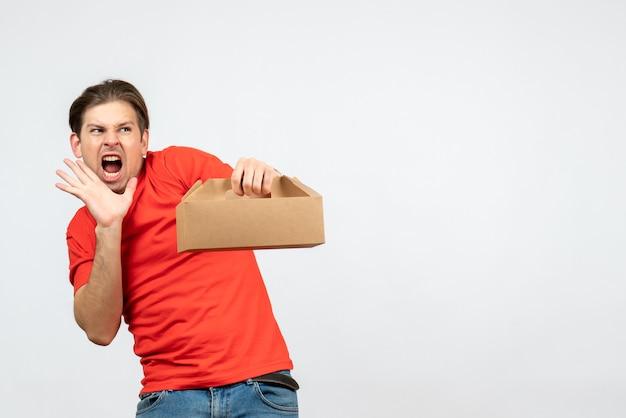 Bovenaanzicht van boze nerveuze en emotionele jongeman in rode blouse met doos op witte achtergrond