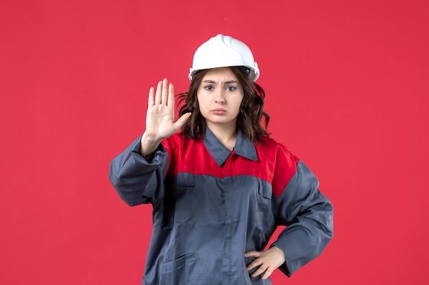 Bovenaanzicht van boze vrouwelijke bouwer in uniform met harde hoed en stopgebaar maken op geïsoleerde rode achtergrond