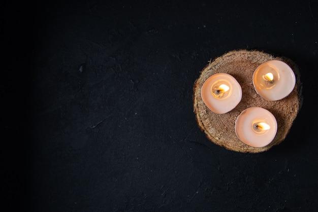 Bovenaanzicht van brandende kaarsen op zwarte muur