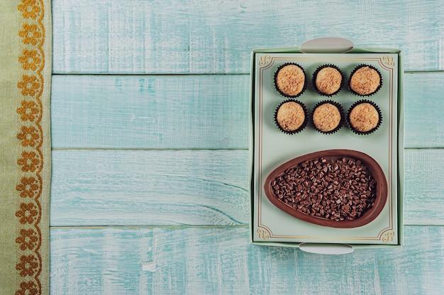 Bovenaanzicht van braziliaans chocolade paasei in een geschenkdoos met braziliaanse snoepbrigadeiro - ovo de chocolate de colher