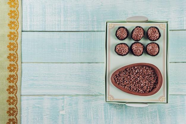Bovenaanzicht van braziliaans chocolade paasei in een geschenkdoos met snoep brigadeiro - ovo de chocolate de colher