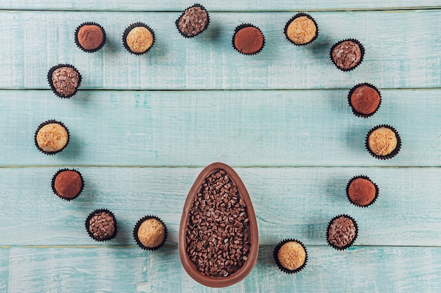 Bovenaanzicht van braziliaans chocolade paasei met braziliaanse snoepjes brigadeiros - ovo de chocolate de colher