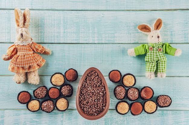 Bovenaanzicht van braziliaanse chocolade paasei met snoep brigadeiros en twee pluche konijnen