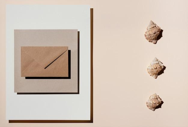 Bovenaanzicht van briefpapier met schelpen met envelop