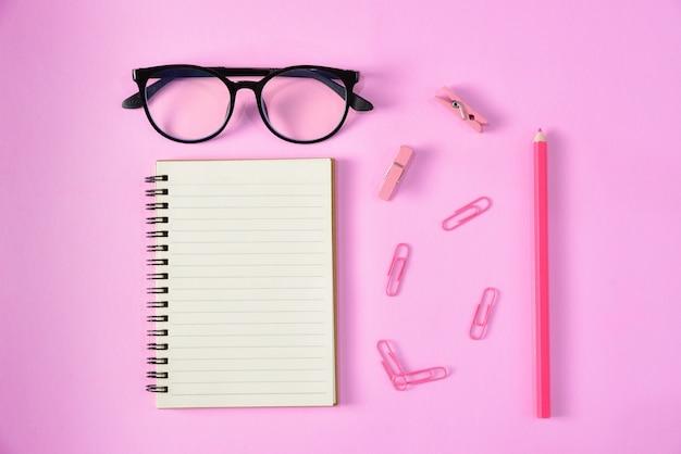 Bovenaanzicht van briefpapier of schoolbenodigdheden met boeken, kleurpotloden, clips en glazen. onderwijs of terug naar school-concept.