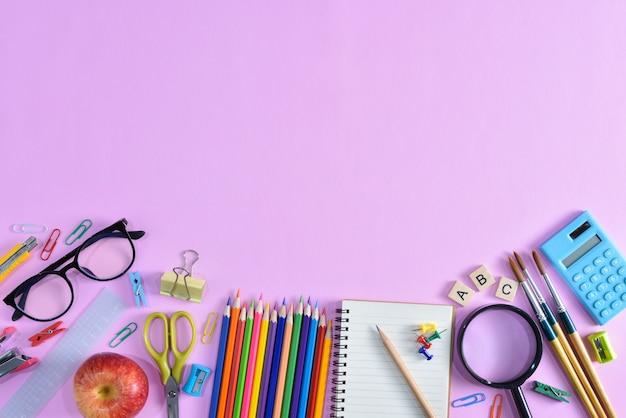 Bovenaanzicht van briefpapier of schoolbenodigdheden met boeken, kleurpotloden, rekenmachine, laptop, clips en rode appel op roze achtergrond.