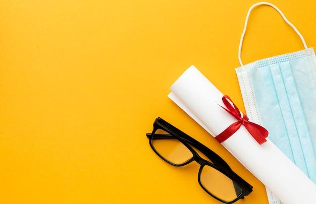 Bovenaanzicht van bril met diploma en medisch masker
