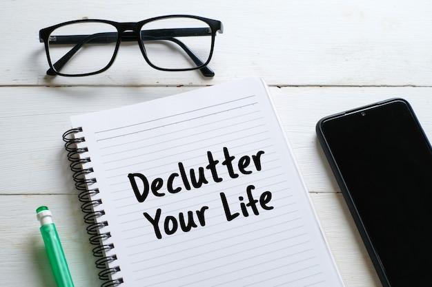Bovenaanzicht van brillen, potlood, plant, pen met handschrift 'declutter your life' op notitieboekje over witte houten achtergrond.
