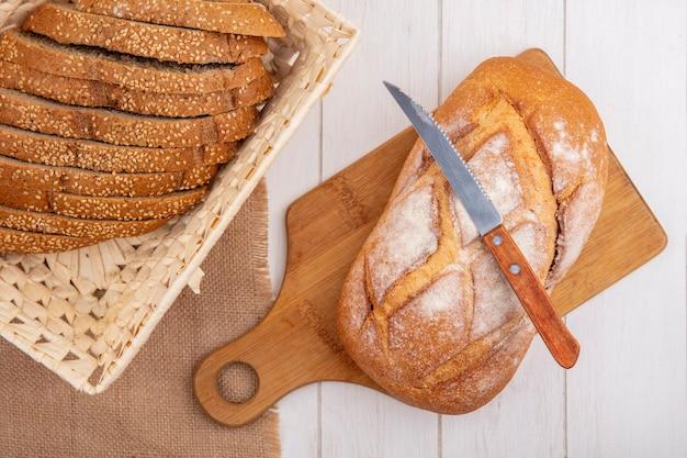 Bovenaanzicht van brood als bruin gesneden gezaaid kolf in mand op zak en knapperig brood met mes op snijplank op houten achtergrond