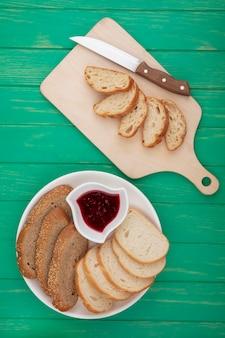 Bovenaanzicht van brood als gesneden croissant met mes op snijplank en gesneden gezaaide bruine kolf en stokbrood degenen met frambozenjam op groene achtergrond