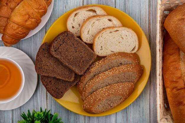 Bovenaanzicht van brood als gesneden gezaaide bruine cob croissant stokbrood rogge en witte in platen en in mand met hete grog op houten achtergrond