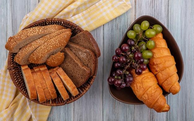Bovenaanzicht van brood als gesneden gezaaide bruine cob rogge en knapperige degenen in mand op geruite doek en kom met croissants en druiven op houten achtergrond