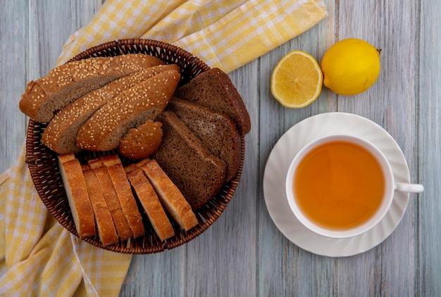 Bovenaanzicht van brood als gesneden gezaaide bruine cob rogge en knapperige in mand op geruite doek en kopje hete grog met half gesneden citroen op houten achtergrond