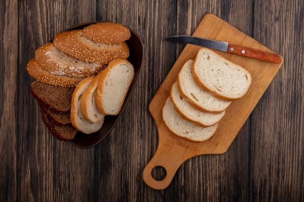 Bovenaanzicht van brood als gesneden gezaaide bruine cob rogge en witte in kom en op snijplank met mes op houten achtergrond