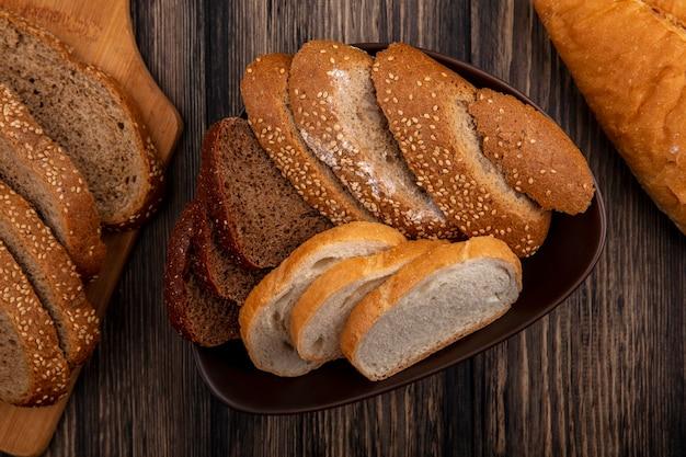 Bovenaanzicht van brood als gesneden gezaaide bruine cob rogge en witte in kom en op snijplank op houten achtergrond