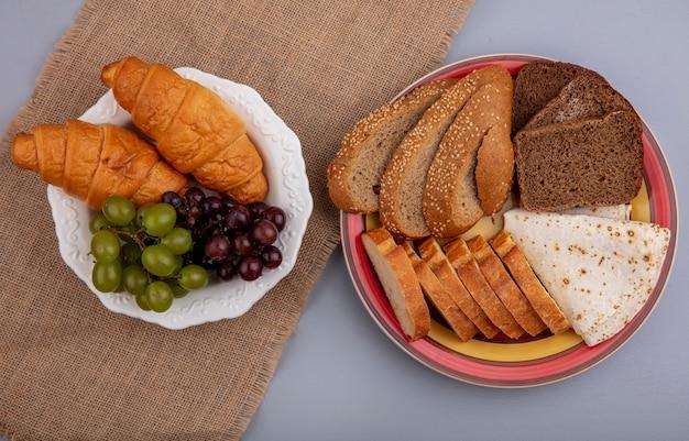 Bovenaanzicht van brood als gesneden gezaaide bruine cob rogge stokbrood en flatbread in plaat op geruite doek met plaat van croissants druiven op zak op grijze achtergrond