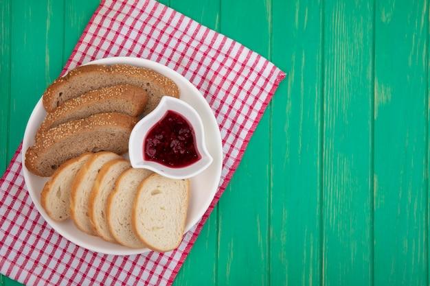 Bovenaanzicht van brood als gesneden gezaaide bruine kolf en stokbrood degenen met kom frambozenjam in plaat op geruite doek op groene achtergrond met kopie ruimte