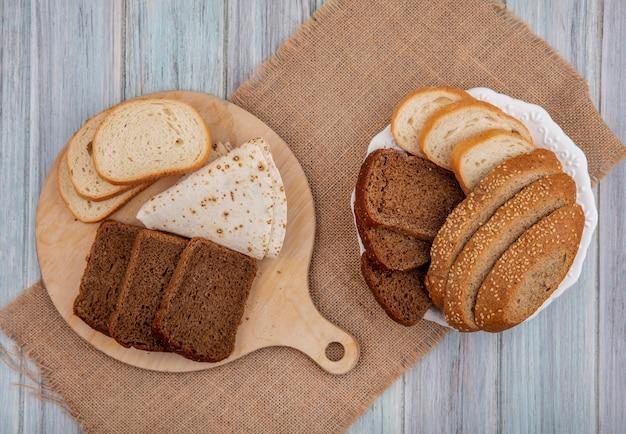 Bovenaanzicht van brood als gesneden rogge wit gezaaid bruine kolf en flatbread op snijplank en in plaat op zak op houten achtergrond