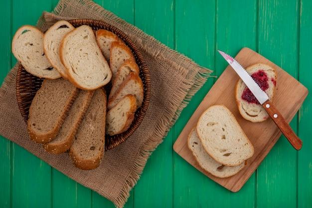 Bovenaanzicht van brood als gezaaide bruine cob en stokbrood plakjes in mand op zak en sneetje brood besmeurd met frambozenjam met mes op snijplank op groene achtergrond