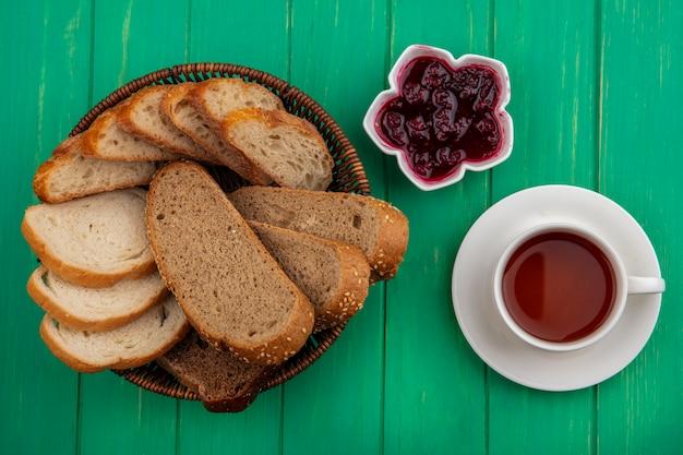 Bovenaanzicht van brood als gezaaide bruine maïskolf en stokbrood plakjes in mand en frambozenjam in kom met kopje thee op groene achtergrond