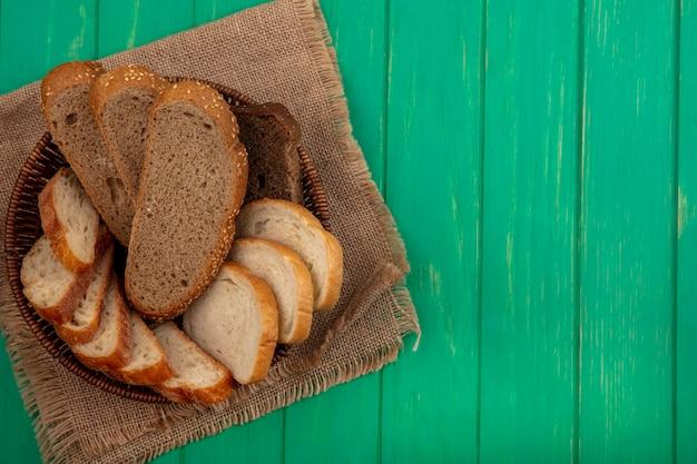 Bovenaanzicht van brood als gezaaide bruine maïskolf en stokbrood plakjes in mand op zak op groene achtergrond met kopie ruimte