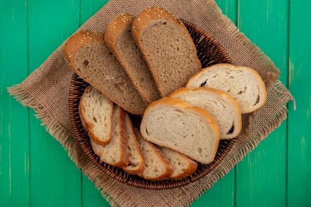 Bovenaanzicht van brood als gezaaide bruine maïskolf en stokbrood plakjes in mand op zak op groene achtergrond