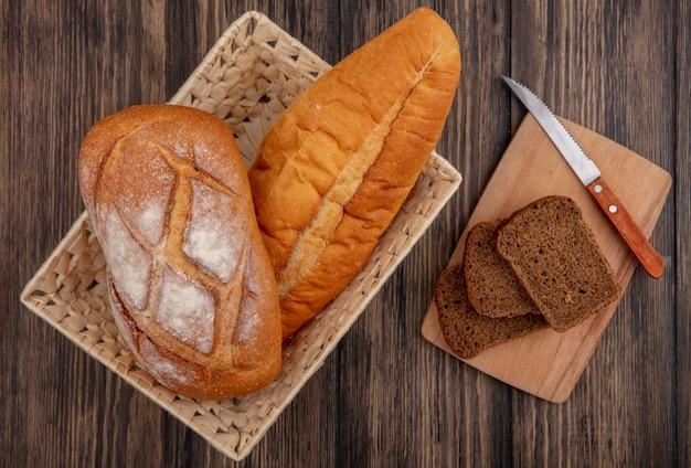 Bovenaanzicht van brood als knapperig en vietnamees stokbrood in mand en gesneden roggebrood met mes op snijplank op houten achtergrond