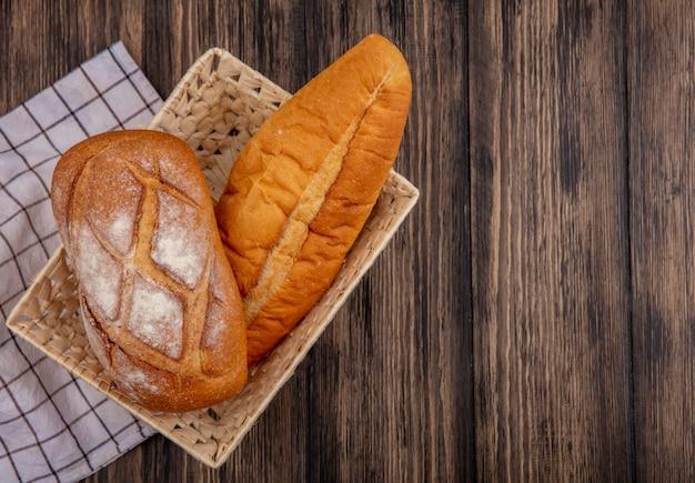 Bovenaanzicht van brood als knapperig en vietnamees stokbrood in mand op geruite doek op houten achtergrond met kopie ruimte