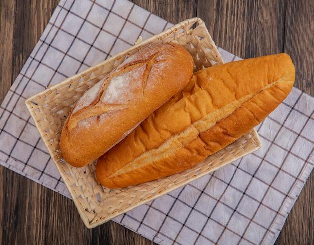Bovenaanzicht van brood als knapperig en vietnamees stokbrood in mand op geruite doek op houten achtergrond