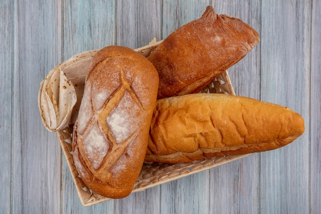 Bovenaanzicht van brood als knapperig flatbread en stokbrood in mand op houten achtergrond