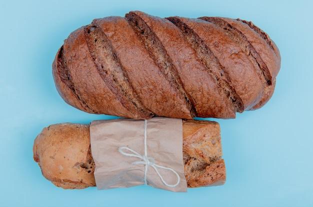 Bovenaanzicht van brood als knapperig stokbrood en zwart brood op blauwe tafel