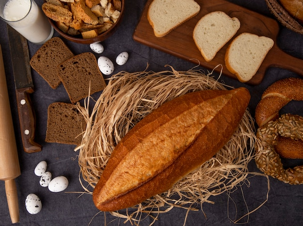 Bovenaanzicht van brood als stokbrood op rogge van stro en wit brood bagel met melk eieren op kastanjebruine achtergrond