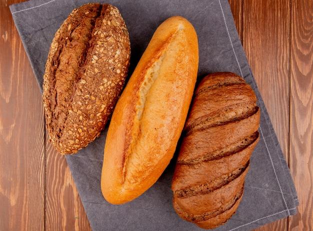 Bovenaanzicht van brood als vietnamees en zwart stokbrood en zwart brood op grijze doek en houten tafel