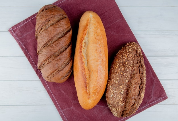 Bovenaanzicht van brood als vietnamees en zwart zaad stokbrood en zwart brood op bordo doek en houten tafel