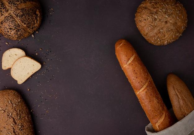 Bovenaanzicht van brood als witte stokbrood maïskolf aan de linker- en rechterkant en kastanjebruine achtergrond met kopie ruimte