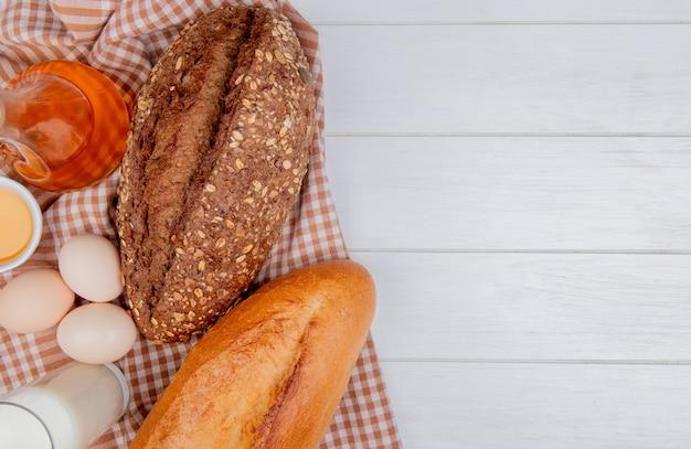 Bovenaanzicht van brood als zwart zaad en vietnamees stokbrood met eieren karnemelk op geruite doek en houten achtergrond met kopie ruimte