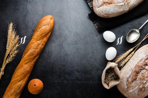 Bovenaanzicht van brood en ingrediënten op zwarte achtergrond