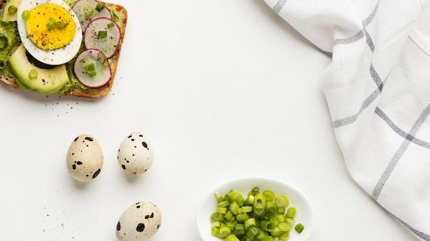 Bovenaanzicht van broodje ei en avocado met tafellaken