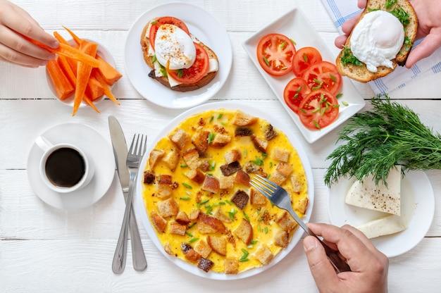 Bovenaanzicht van broodje gepocheerd ei, omelet, verse groenten, koffie en meer op een witte houten tafel