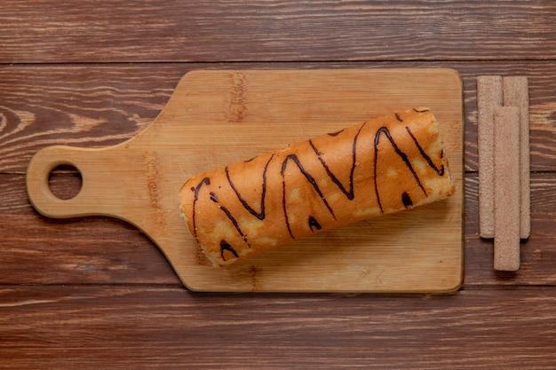 Bovenaanzicht van broodje op snijplank met koekjes op houten tafel