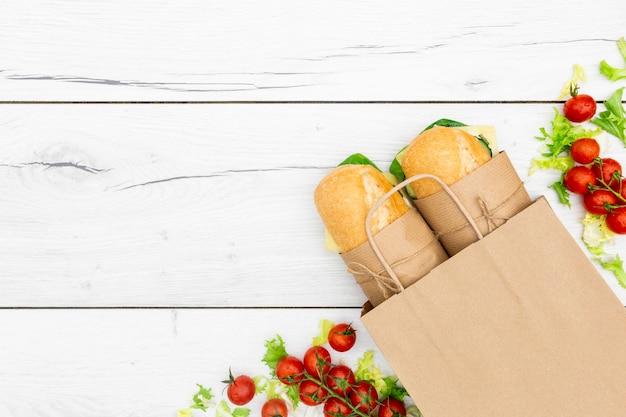 Bovenaanzicht van broodjes met tomaten en kopie ruimte
