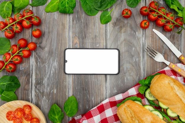 Bovenaanzicht van broodjes met tomaten en smartphone