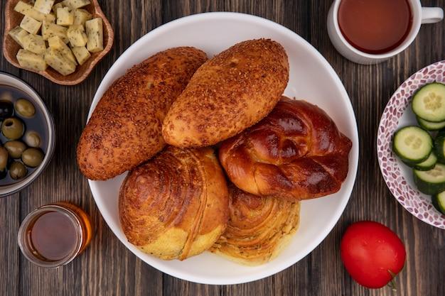Bovenaanzicht van broodjes op een bord met honing met olijven, groenten en gehakte plakjes kaas op een houten achtergrond