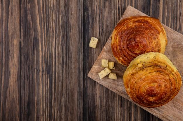 Bovenaanzicht van broodjes op een houten keukenbord met gehakte plakjes kaas op een houten achtergrond met kopie ruimte