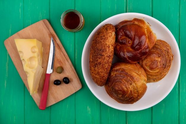 Bovenaanzicht van broodjes op een witte plaat met kaas op een houten keukenplank met mes op een groene houten achtergrond