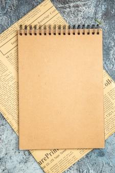 Bovenaanzicht van bruin notitieboekje op krant op grijze achtergrond
